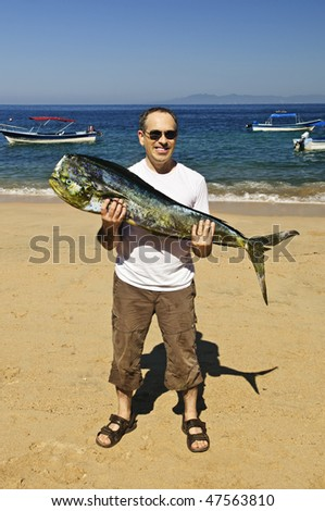 Happy tourist holding his big fish catch after fishing trip in Mexico