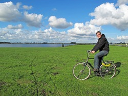 Happy tourist in Netherlands on a bike in polder.