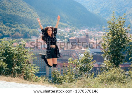 Happy Tourist Jumping in Front of Panoramic City View. Cheerful woman expressing excitement for touristic experience