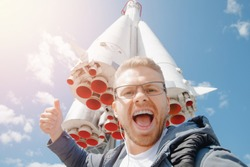 Happy tourist man taking selfie photo on background of rocket spaceport, concept of commercial space flights, Mars colonizers.