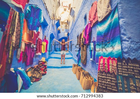 happy tourist on the blue streets of Chefchaouen, Morocco. caucasian girl posing and admiring the medina of the Blue City in Morocco, Africa. Narrow alley with blue houses in Chefchaouen