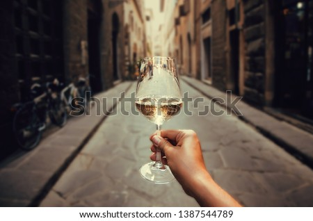 Happy tourist walking on narrow streets with white wine glass in hand. Enjoying life concept. #1387544789