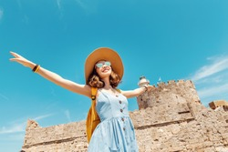 Happy tourist woman on vacation posing with hat and backpack in front of the old ruined fort and lighthouse in Rhodes, Greece