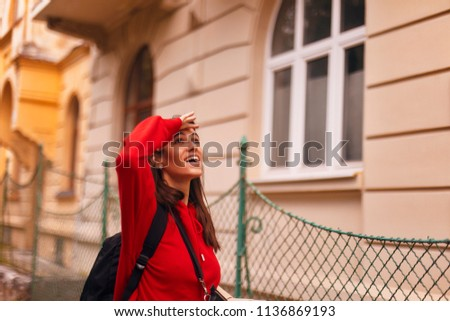 happy tourist woman walking on the street with nice architecture. brunette girl is looking at something. wearing red hoodie and with packed black bag #1136869193