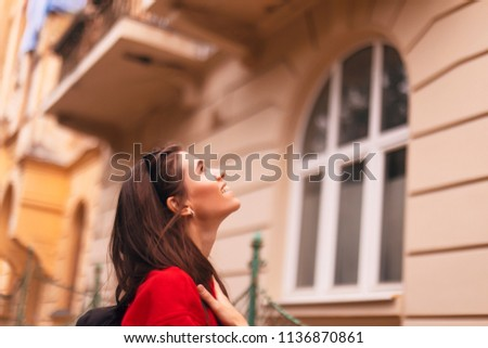 happy tourist woman walking on the street with nice architecture. brunette girl is looking at building. she is wearing red hoodie and packed black bag #1136870861