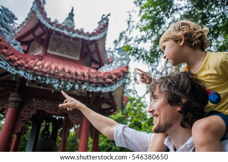 Happy tourists dad and son in Long Son Pagoda. Travel to Asia concept. Traveling with a baby concept.