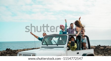 Happy tourists friends doing excursion on desert in convertible 4x4 car - Young people having fun traveling together - Friendship, tour, youth lifestyle and vacation concept - Focus on left girl