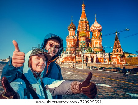 Happy tourists sightseeing city with fingers up next to Saint Basil's Cathedral. Red Square, Moscow, Russia. Holiday, travel, recreation. Winter season, bright colors, clear blue sky #720995551