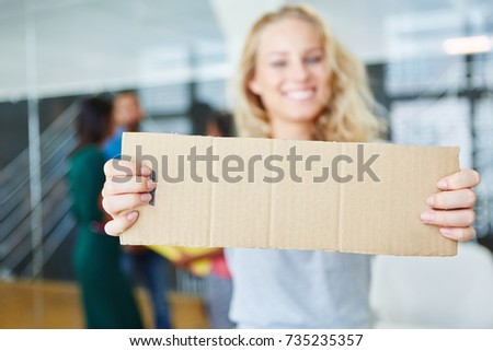 Happy trainee holding blank sign for business message