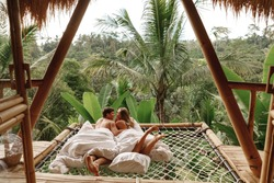 Happy travel couple on hammock balcony of bamboo tree house with jungle nature view. vacation in beaitiful hidden place, honeymoon on Bali island