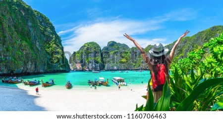 Happy travel vacation destination, Wide panorama banner nature landscape, Travelers summer holiday outdoor Tourism woman with hand up relaxing beautiful famouse beach Maya bay, Landmark Thailand, Asia