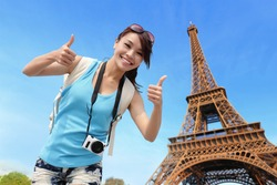 Happy travel woman in Paris with Eiffel Tower and she show thumb up, asian beauty