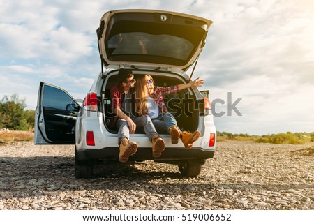 Happy traveler couple sitting in car open trunk and watch the sunrise