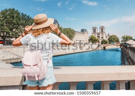 Happy traveler girl blogger takes photos of Notre Dame De Paris and the river Seine for her social media