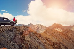 Happy Traveler man sitting on his car on mountains top. 4x4 travel trekking