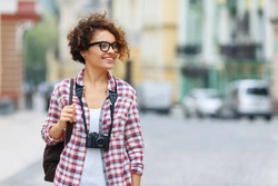 Happy traveler. Pretty blissful positive girl holding photo camera and expressing gladness while walking around the city