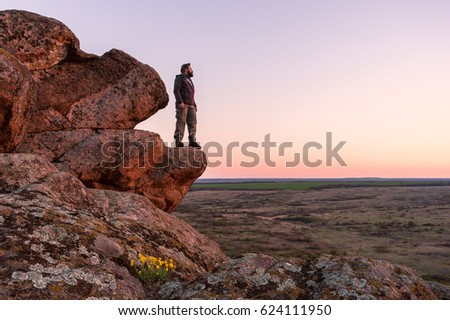 Happy traveler stand on a mountain top and looking ahead. Active, healthy lifestyle. Traveling concept background #624111950
