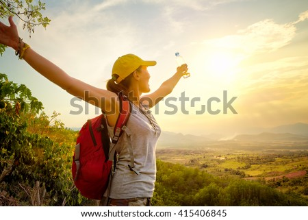 Happy traveler with backpack and bottle of water standing on top of mountain and enjoying valley view with raised hands.\ Mountains landscape, travel to Asia, happiness emotion, summer holiday concept