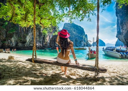 Happy traveler woman in bikini relaxing on swing under tree looking destinations sea beach, Lao Lading island, Andaman sea, Krabi, Phuket, Travel Thailand, Tourist Asia, Summer holiday vacation trip