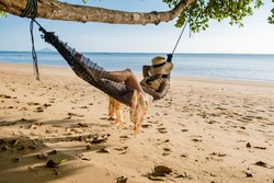 Happy traveler woman in hammock relaxing on the swing and looking beautiful nature, Andaman sea, Krabi, Tourist sea beach Thailand, Asia, Summer holiday vacation travel trip. European man and an Asian