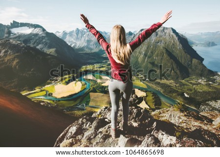 Happy traveler woman raised arms standing on cliff over mountains valley landscape Travel healthy Lifestyle adventure vacations in Norway #1064865698