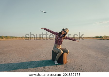 Happy traveler woman sits on vintage suitcase on road and makes a gesture of flight. With vintage retro instagram filter