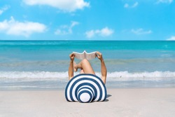 Happy traveller Asian woman lie down to reading a book at tropical beach on vacation. Summer on beach concept.