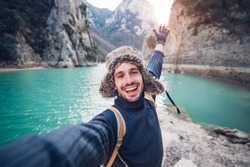 Happy traveller man takes a selfie photo on a lake at the mountain
