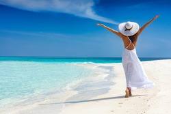 Happy traveller woman in white dress enjoys her tropical beach vacation