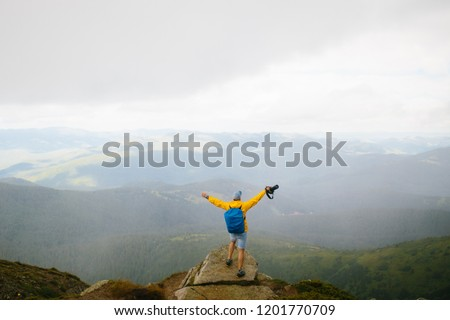Happy travelling photographer standing raising arms with happiness to the sky. Man relaxing and enjoying life on nature outdoors at the clif. Man in yellow jaсket with blue bagpack and cap with camera