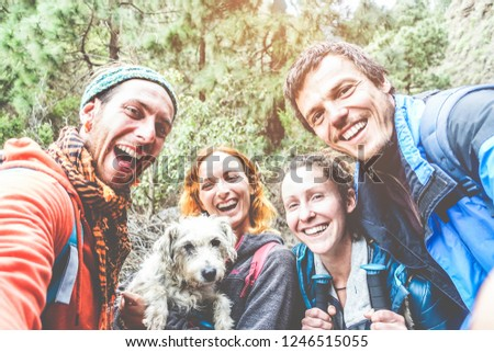 Happy trekkers people taking selfie for social network story with their dog - Young hikers friends having fun on mountain excursion day - Technology trends and sport concept - Main focus on men faces
