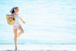 happy trendy middle age woman in white t-shirt and pink shorts with beach straw bag holding orange flip flops, listening to the music with headphone and dancing on the ocean shore.