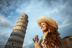 happy trendy middle aged traveller woman in floral dress with retro camera and hat near Leaning Tower in Pisa, Italy.