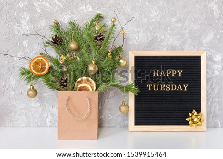 Happy Tuesday text on black letter board and festive bouquet of fir branches with christmas decor in craft package on table. Template for postcard, greeting card Concept Hello winter Tuesday. #1539915464