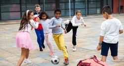 Happy tween girls and boys of different nationalities playing football in schoolyard during break in lessons on warm fall day.