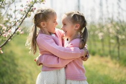 Happy twin sisters hug against the background of a green blooming Apple orchard. The sisters look at each other and laugh.