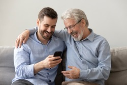 Happy two age generations men family old father embracing young grown adult son having fun enjoying using smart phone bonding watching funny social media video using mobile apps at home sit on sofa