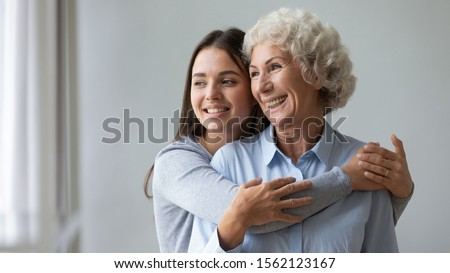 Happy two age generations women family young adult woman daughter granddaughter embrace smiling old elder lady grandma mom look through window intro good future dream enjoy wellbeing together concept