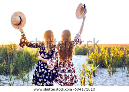 Happy two beat friends girls poring on countryside, enjoy their countryside trip, hugs and positive mood, stylish dress, boho style, straw hats. Posing back, travel experience . #694171810
