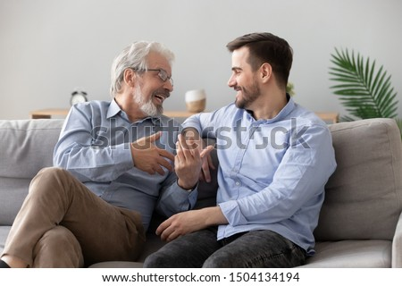 Happy two generations male family old senior mature father and smiling young adult grown son enjoying talking chatting bonding relaxing having friendly positive conversation sit on sofa at home
