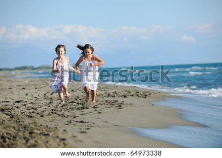 happy two little girls have fun and joy time at beautiful beach while running from joy