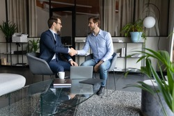 Happy two male partners shaking hands, making agreement after negotiations in modern office. Smiling young leader ceo in suit praising young employee, thanking for good job, achievement concept.