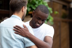 Happy two multiracial male best friends greeting, african guy embracing caucasian buddy at meeting outdoor, smiling multi-ethnic young men hug say hello, multicultural friendship reunion concept