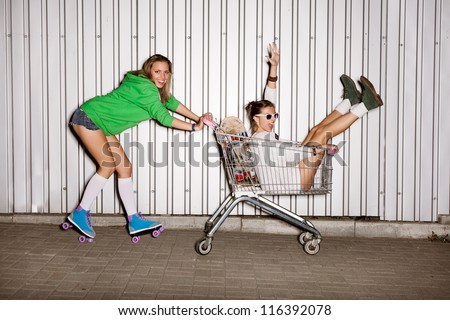 Happy two naughty women with shopping cart. outdoors