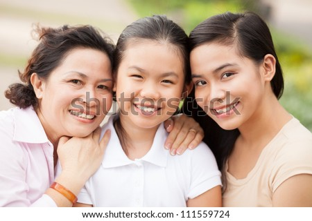 Happy two sisters and grandmother smiling at camera