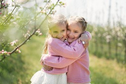 Happy two twin sisters are hugging against the background of a green blossoming apple orchard.