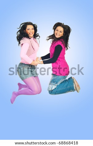Happy two women jumping and holding their hands over blue background