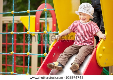 Happy two-year child on slide playground area