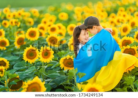 Happy Ukrainian children hug and wrap around a large Ukrainian flag against the backdrop of a sunflower field. A boy and a girl celebrate the Independence Day of Ukraine. Copy space. Foto d'archivio ©