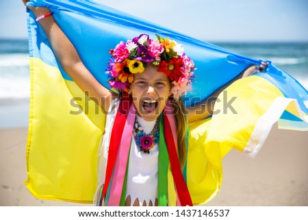 Happy Ukrainian girl carries fluttering blue and yellow flag of Ukraine against blue sky and sea background. Ukrainian flag is a symbol of independence. Celebrate Constitution day, Kyiv day, Kiev day #1437146537